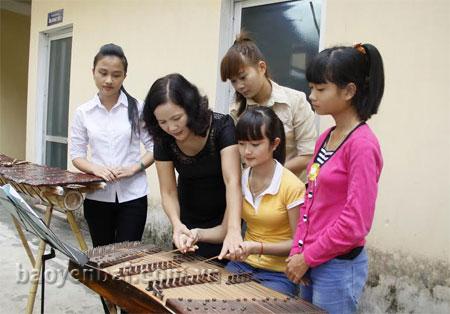 Cô Kim Phụng hướng dẫn các em học sinh khoa Âm nhạc dân tộc chơi đàn tam thập lục. (Ảnh: Ngọc Đồng)