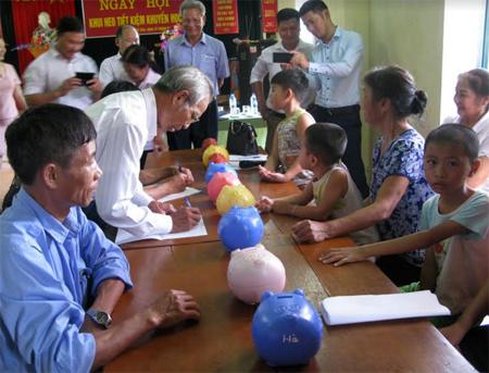 Nuôi lợn đất tiết kiệm để khuyến học trong gia đình, là hình thức mới đang được nhân rộng. (Ảnh: Nhân dân thôn Thanh Sơn, xã Tuy Lộc, thành phố Yên Bái mổ lợn tiết kiệm lo cho việc học hành của con cháu).