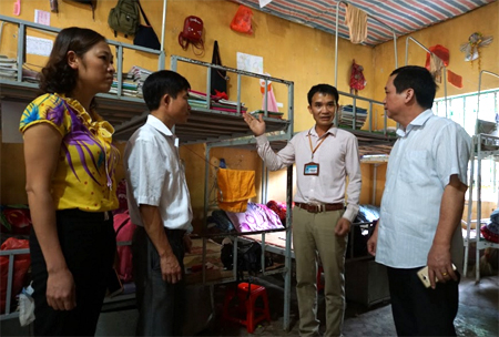 Thầy giáo Nguyễn Đức Thành (thứ 2, bên phải) giới thiệu nơi ở bán trú của học sinh nhà trường.