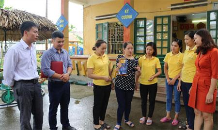Cán bộ Trung tâm Y tế thành phố Yên Bái hướng dẫn giáo viên Trường mầm non Hướng Dương, xã Tuy Lộc, thành phố Yên Bái cách sử dụng dung dịch khử khuẩn CloraminB.