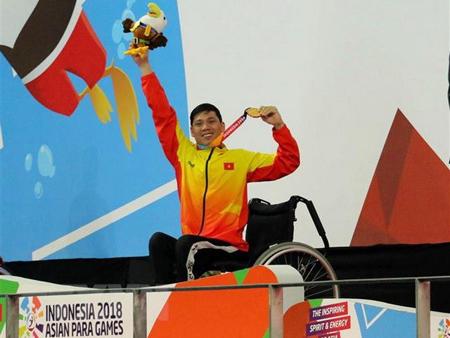 Vận động viên Võ Thanh Tùng tự hào giơ cao tấm Huy chương vàng thứ 3 tại Asian Para Games 2018.