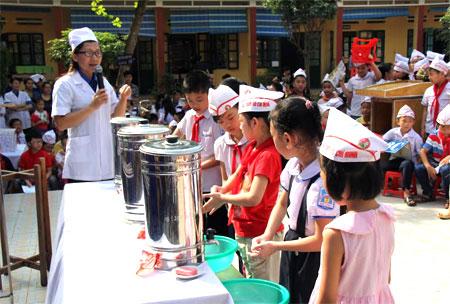 Cán bộ Trung tâm Kiểm soát bệnh tật hướng dẫn học sinh Trường Tiểu học Kim Đồng, thành phố Yên Bái rửa tay bằng xà phòng trước khi ăn.