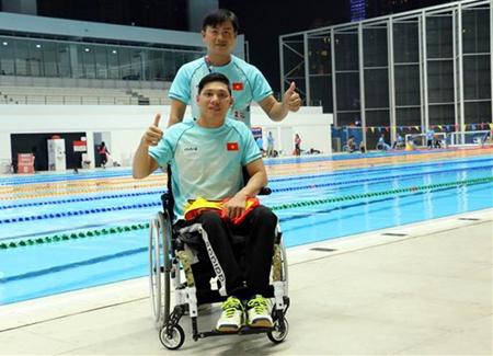 Võ Thanh Tùng (phía trước) cùng huấn luyện viên sau khi kết thúc nội dung thi đấu bơi 50m tự do.