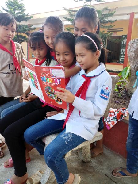 Em Trần Thị Thanh Hậu (thứ 2, bên phải) trao đổi bài với các bạn cùng lớp.