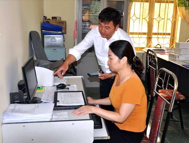 Cán bộ Phòng Dân tộc huyện Trạm Tấu trao đổi việc thực hiện chính sách dân tộc trên địa bàn.