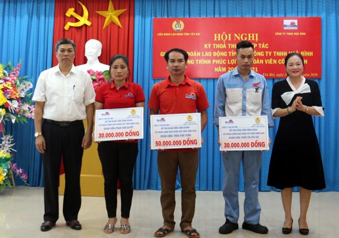 """Bà Bùi Thị Sửu (bên phải) - Giám đốc Công ty TNHH Hòa Bình và Công đoàn cơ sở Công ty trao hỗ trợ nhà """"Mái ấm nghĩa tình"""" cho 3 công nhân của doanh nghiệp."""