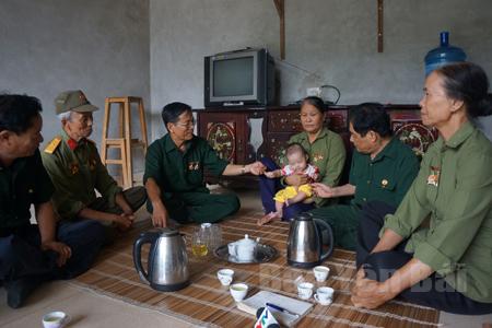Cô Phạm Thị Thìn (người bế cháu bé) xúc động trong sự sẻ chia, thông cảm của đồng đội.