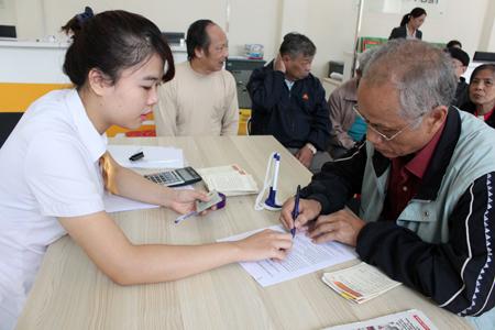 Nhân viên Bưu điện huyện Yên Bình hướng dẫn người dân kê khai thông tin trên mẫu phiếu TK01.