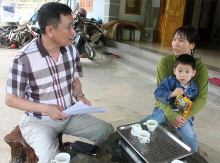 Cán bộ Bảo hiểm xã hội huyện Yên Bình tuyên truyền chính sách bảo hiểm y tế hộ gia đình cho người dân.