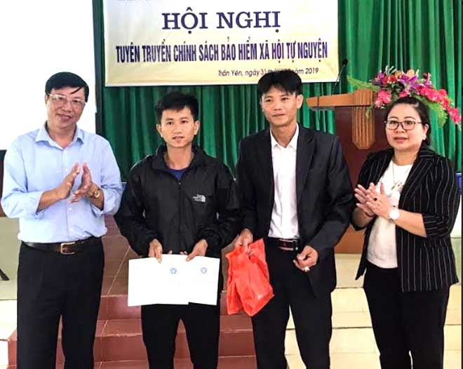 Giám đốc Bảo hiểm xã hội huyện Trấn Yên (ngoài cùng bên trái) trao sổ bảo hiểm xã hội cho người dân tham gia bảo hiểm xã hội tự nguyện.