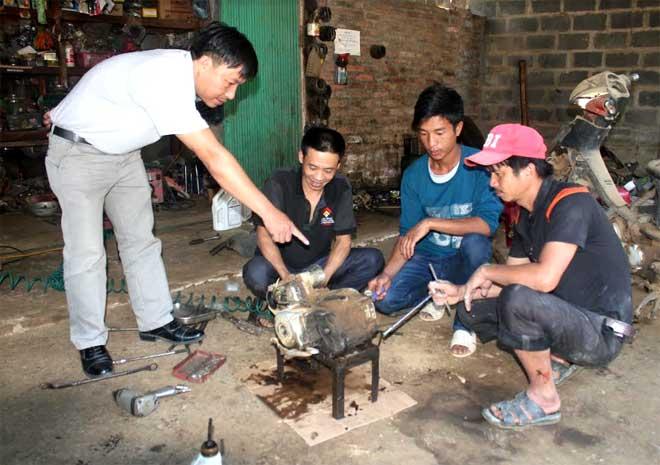 Cán bộ Trung tâm GDNN - GDTX huyện Trạm Tấu hướng dẫn học viên học nghề sửa chữa xe máy.