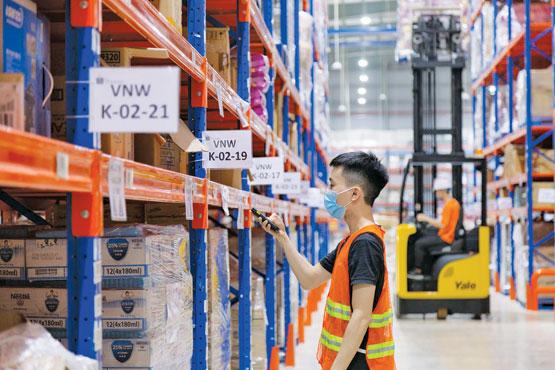 Các sàn thương mại điện tử đưa ra nhiều chương trình ưu đãi mới trong thời điểm cuối năm. Trong ảnh: Nhân viên kho hàng sàn thương mại điện tử Shopee chuẩn bị hàng giao cho khách.