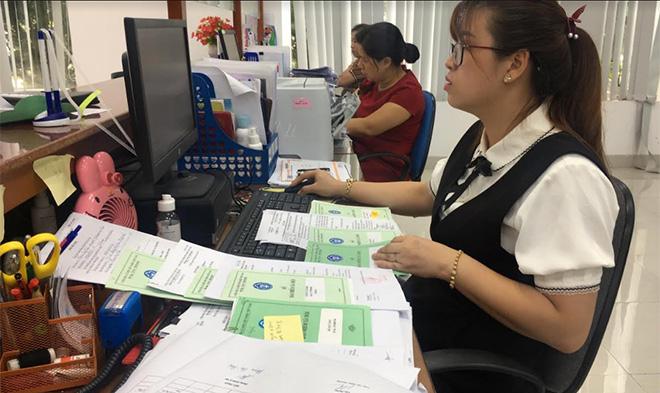 Cán bộ Bảo hiểm xã hội tỉnh Yên Bái chốt sổ bảo hiểm cho người lao động.