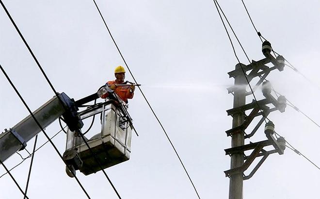 Công nhân Công ty Điện lực Yên Bái vệ sinh sứ cách điện bằng nước áp lực cao.