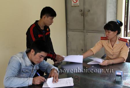 Cán bộ Đội Cảnh sát giao thông - Trật tự - Cơ động, Công an huyện Yên Bình hướng dẫn thủ tục cho người dân.