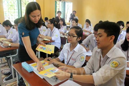 Giáo viên Trường THPT Lý Thường Kiệt, thành phố Yên Bái phát tờ gấp tuyên truyền về BHYT học sinh, sinh viên đến học sinh trong trường.