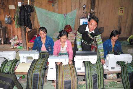 Anh Giàng A Măng hướng dẫn phụ nữ trong thôn sử dụng máy dệt thổ cẩm.