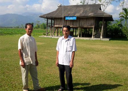Ông Đồng Văn Đức (bên phải) cùng Trưởng thôn Bản Vệ bàn bạc công tác tổ chức Ngày hội Đại đoàn kết các dân tộc.