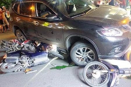 Hàng loạt xe máy bị cuốn vào gầm chiếc xe hơi 4 chỗ trên đường sau va chạm.