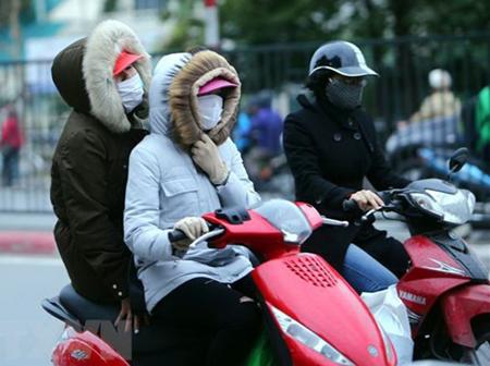 Người dân Hà Nội trang bị áo ấm chống rét, trên đường Giải Phóng.