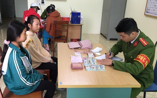 Em Chu Lệ Ngân và Nguyễn Hảo Tâm- học sinh Trường THCS Quang Trung đem chiếc túi xách nhặt được đến trụ sở Công an phường Đồng Tâm trình báo và giao nộp cho Công an phường.