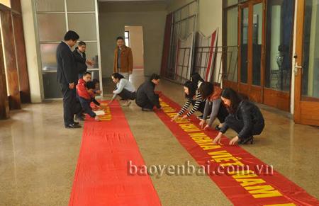 Cán bộ Trung tâm Văn hóa tỉnh chuẩn bị băng rôn, pano, áp phích trang trí trước ngày diễn ra Đại hội XII của Đảng tại trung tâm thành phố.