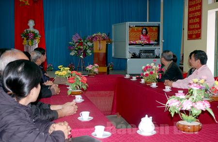 Người dân khu dân cư Thắng Lợi 2, phường Nguyễn Thái Học, thành phố Yên Bái theo dõi phiên bế mạc Đại hội XII của Đảng sáng 28/1.
