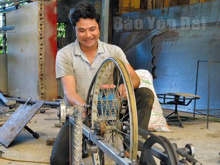 Anh Bùi Sỹ Tới bên sản phẩm cơ khí tự sáng chế.