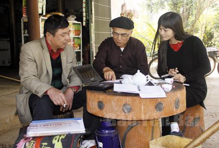 Ông Lạc Văn Sinh (giữa) trao đổi với cán bộ văn hóa huyện Yên Bình về các tài liệu đã sưu tầm Sình ca Cao Lan.
