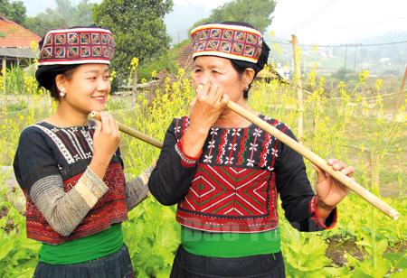 Nghệ nhân Đặng Thị Thanh hướng dẫn các thiếu nữ thổi sáo cúc kẹ.