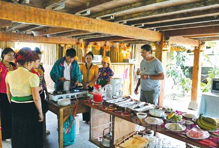 Khách du lịch thưởng thức văn hóa ẩm thực của người Thái Mường Lò. (Ảnh: Thành Trung)