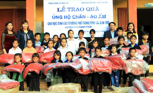 Đại diện lãnh đạo Hội Khuyến học tỉnh và huyện Mù Cang Chải trao chăn, áo ấm cho học sinh Trường PTDT bán trú TH&THCS Khao Mang.