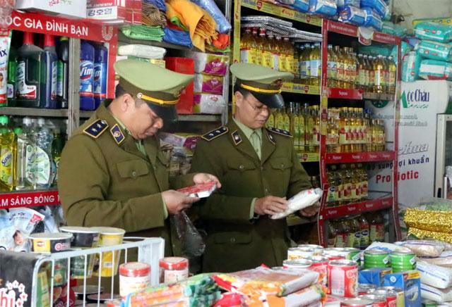 Cán bộ QLTT huyện Yên Bình kiểm tra việc thực hiện ghi nhãn hàng hóa trên bao bì sản phẩm tại các cơ sở kinh doanh.