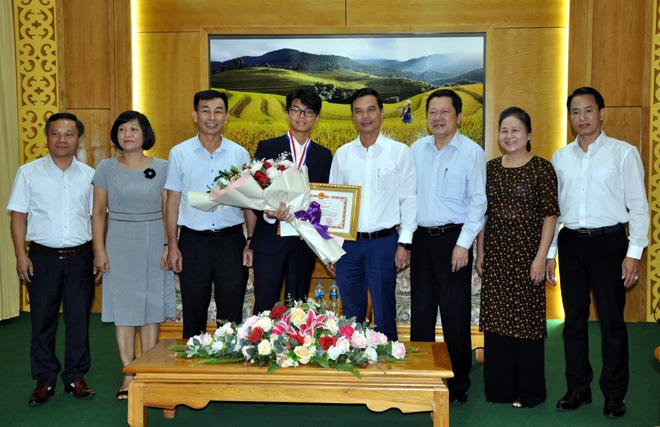 Đồng chí Dương Văn Tiến - Phó Chủ tịch UBND tỉnh và các đồng chí lãnh đạo Sở Giáo dục và Đào tạo trao bằng khen và phần thưởng cho em Nguyễn Đình Hoàng giành Huy chương Bạc, trong Kỳ thi Olympic Hóa Học năm 2019.
