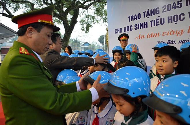 Lãnh đạo Ban An toàn giao thông tỉnh hướng dẫn học sinh đội mũ bảo hiểm.
