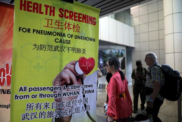 Hành khách đi qua tấm banner cung cấp thông tin về dịch viêm phổi cấp ở Vũ Hán tại điểm rà quét thân nhiệt tại ga đến quốc tế ở sân bay Kuala Lumpur - Ảnh: REUTERS