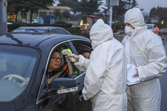 Các nhân viên y tế mang thiết bị bảo hộ kiểm tra thân nhiệt của một tài xế tại điểm kiểm tra trên đường cao tốc ở thành phố Đằng Châu, tỉnh Sơn Đông hôm 26/1