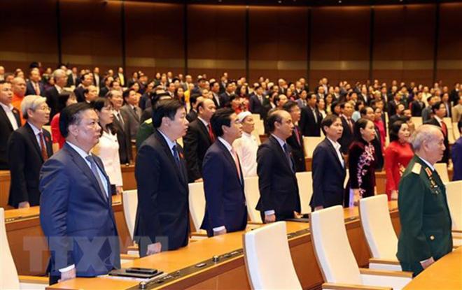Các đại biểu thực hiện nghi lễ chào cờ tại một phiên họp.
