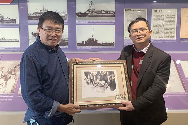 Ông Trần Thọ Phi Hổ (trái) tặng những bức ảnh quý chụp ở đảo Hoàng Sa cho ông Lê Tiến Công - phó giám đốc phụ trách Nhà trưng bày Hoàng Sa