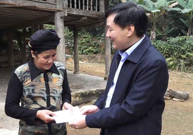 Bí thư Huyện uỷ Lục Yên Hoàng Hữu Độ tặng quà Tết cho hộ bà Hoàng Thị Chấn, thôn Ngòi Tàu, xã Liễu Đô-một trong những hộ tự nguyện viết đơn xin  thoát nghèo
