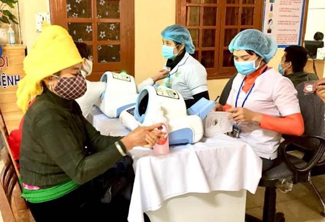 Người dân sử dụng dung dịch sát khuẩn tay trước khi đăng ký khám bệnh tại Khoa Khám bệnh, Bệnh viện Đa khoa khu vực Nghĩa Lộ