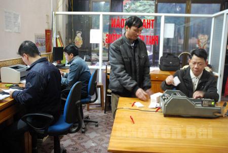 Anh Hoàng Thế Vĩnh (đứng bên trái) nộp bảng kê và cuống vé tại Văn phòng Xổ số Nguyễn Thái Học.