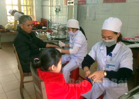 Các y, bác sỹ Trung tâm Y tế huyện Yên Bình khám, chữa bệnh cho người dân.