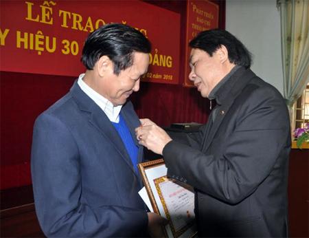 Đồng chí Nông Thụy Sỹ - Bí thư Đảng bộ, Tổng Biên tập Báo Yên Bái gắn Huy hiệu 30 năm tuổi Đảng cho đồng chí Phí Văn Nam – Phó Tổng biên tập.