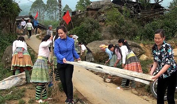 Phụ nữ thôn Tà Xùa chung tay giữ gìn vệ sinh đường thôn sạch đẹp.