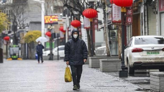 Một người dân đi bộ trên phố ở Vũ Hán, tâm dịch COVID-19.