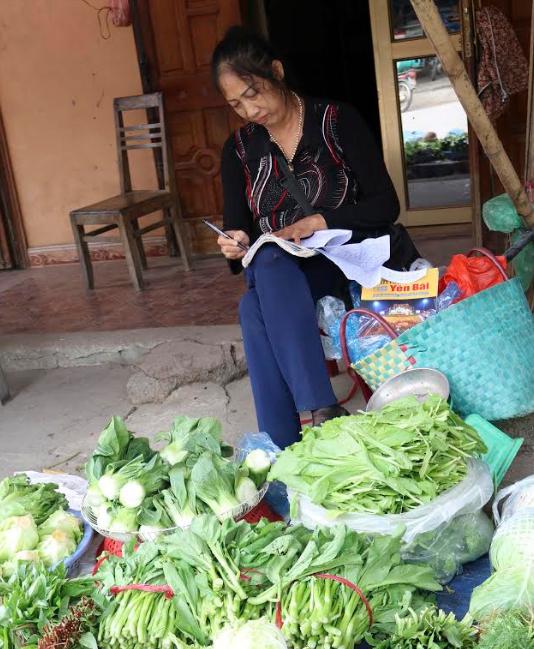 Chị Trần Thị Hợp say mê viết sách bên sạp rau bán vỉa hè.