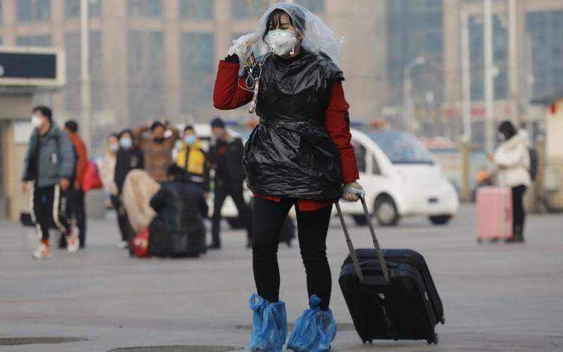 Một nữ hành khách ở ga tàu hỏa Bắc Kinh dùng túi nylon che đầu, chân và thân để phòng virus corona chủng mới Covid-19.