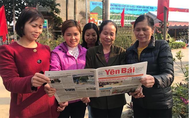 Nhân dân xã Việt Thành phấn khởi theo dõi tin tức về Đại hội trên báo Đảng. (Ảnh: Hồng Oanh)