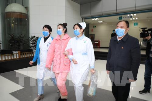 Bệnh nhân nhiễm COVID-19 (thứ 2, trái) xuất viện sau khi được chữa khỏi tại bệnh viện ở tỉnh Quý Châu, Trung Quốc, ngày 8/2/2020.